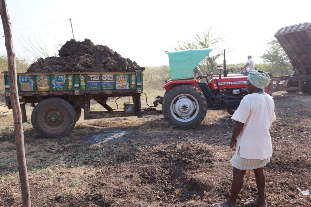 A tractor delivers a load of dirt to the land for the construction of the Good News Visions Prayer Hall, with Yesupadem looking on.