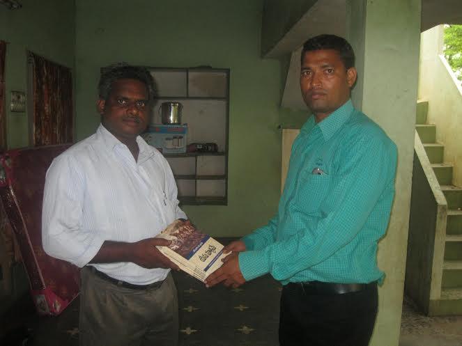 Pr Daniel receiving the Jesus Only books from Pr Joseph