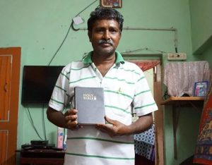Raju holds his new Bible, joyful to have found the Gospel.