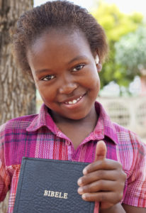 Smiling serene and content little girl proudly holding onto her Bible..